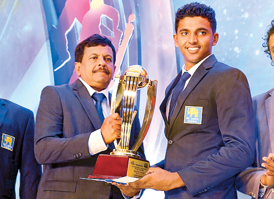 Lasith Croosepulle from  Maris Stella College receives the Best Batsman's award from Kamal Wijesuriya the Deputy General Manager of Commercial Printing Lake House