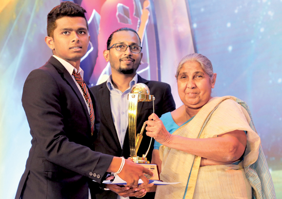 Best Batsman in Division II Raveen Yasas of Devapathiraja College receiving his Award from Chief Editor of Dinamina Pushpa Rowel