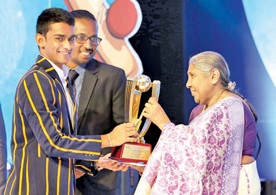 Pasindu Sooriyabandara of Royal College receiving the best batsman's award from Pushpa Rowel (Editor in Chief of Dinamina)