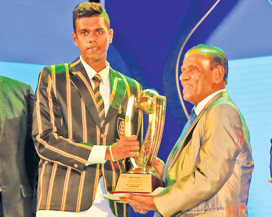 Best batsman Navod Paranavithana of Mahinda College accepts his award from ANCL Chairman, President's Counsel W. Dayaratne