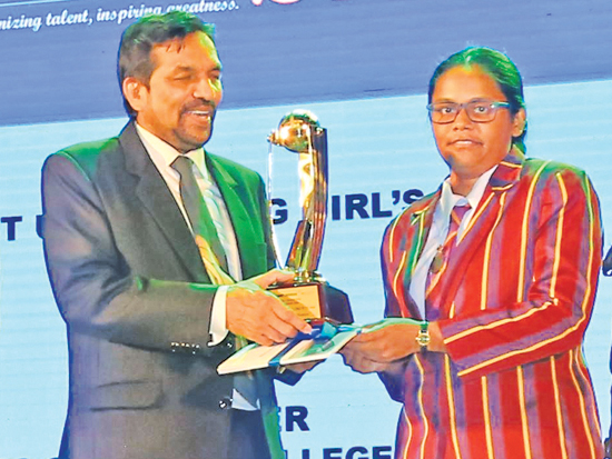 Captain of the best up-and-coming girls school Princess of Wales College receives the award from Media and Information Ministry Secretary Jagath P Wijeweera